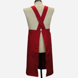 Image shows the back of a red cross back apron on a vintage mannequin