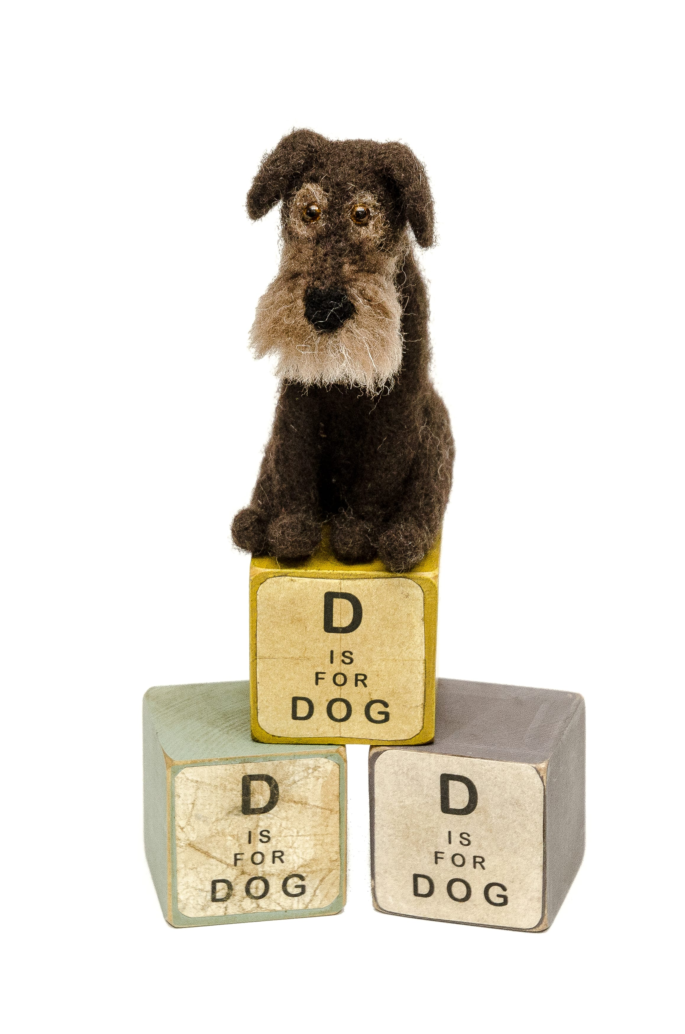 Image shows a small felted terrier type dog sat on top of 3 vintage wooden blocks with D for Dog written on them