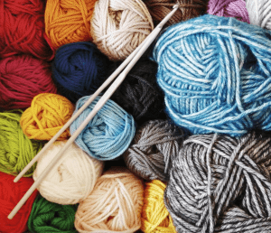 Image showing brightly coloured balls of wool of varying sizes, all stood on their end with 2 crochet hooks laid across the top.