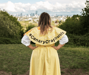 The image shows a woman with her back to the camera looking out over a city from a green hill wearing a yellow cape with the words #canary craftivists in black, a yellow skirt and white blouse. She has long dark blond hair