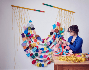 Image shows a woman in a blue cardigan with her hair up and glasses on, she has pieces of wool in her hand and behind her is a wall hanging made up of various felted wool shapes linked together in garlands.